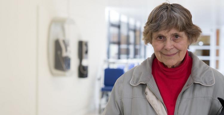 older person standing in hospital corridor