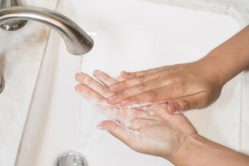 Hands washing over a sink with soap