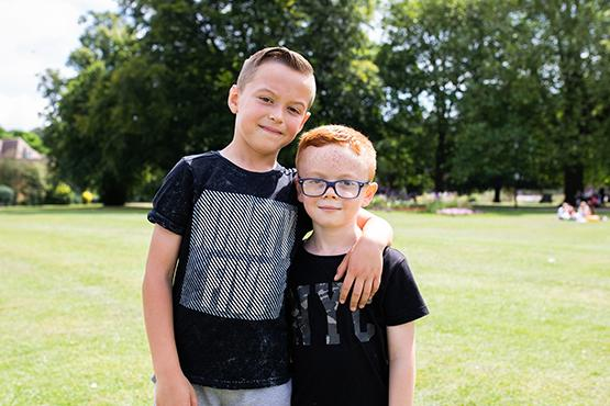 two children standing in the park - the older child has his arm around the younger child's shoulder