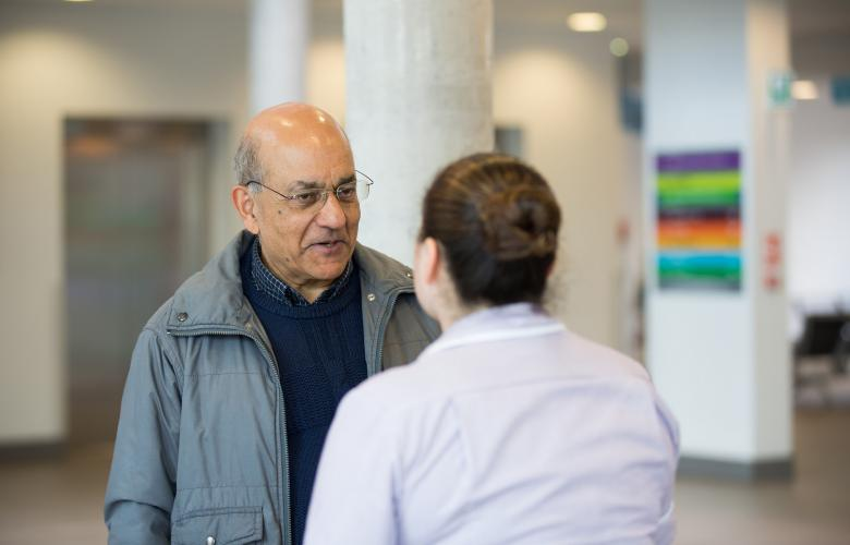 Man talking to health professional in waiting room
