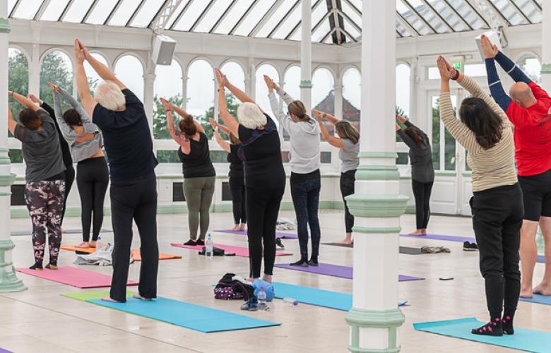 A group of people doing an indoor yoga session. The photo is taken from behind the group, and shows about 15 people, of various ages and genders, doing an upright yoga pose.